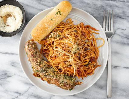 plate with baked crispy spaghetti, a breadstick, and italian sausage