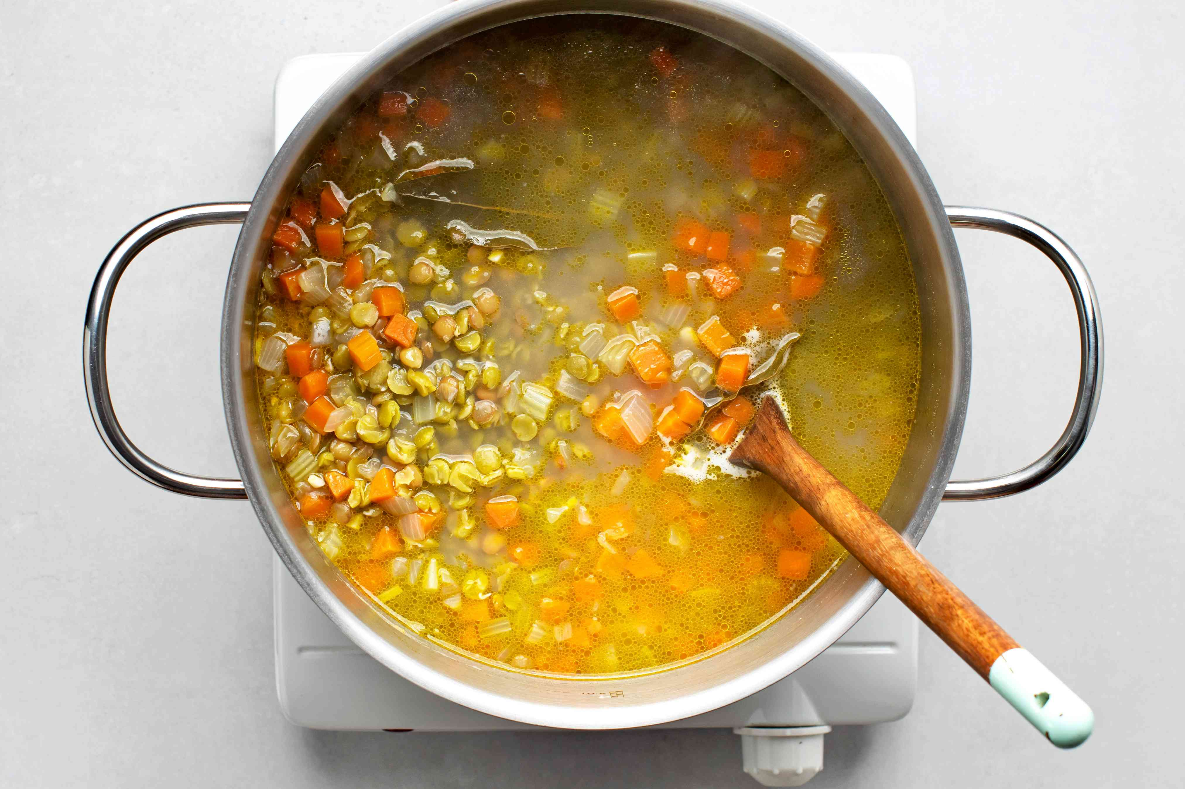 Add the split peas, lentils, and water to the vegetable mixture in the pot