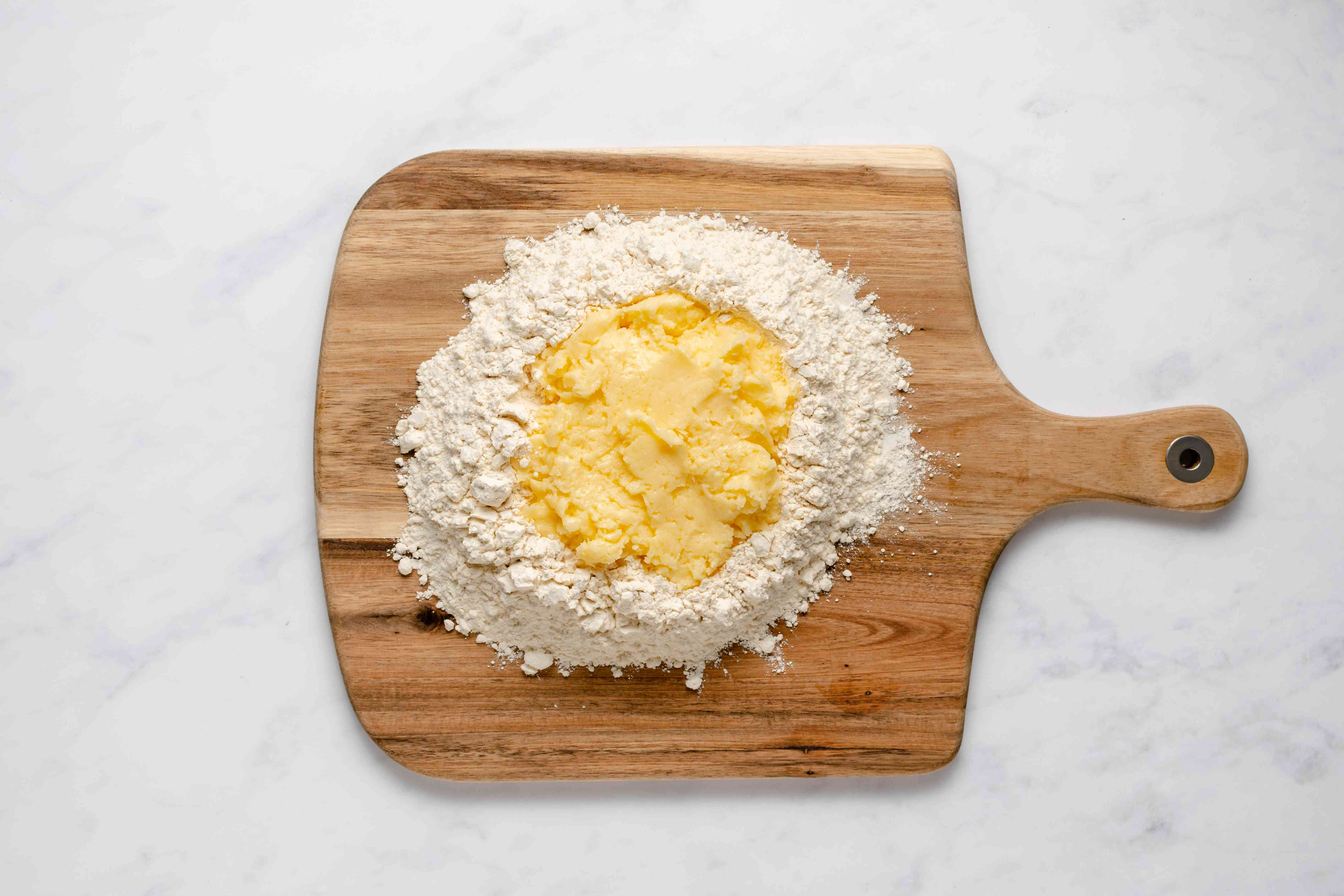 butter mixture in a flour well on a cutting board