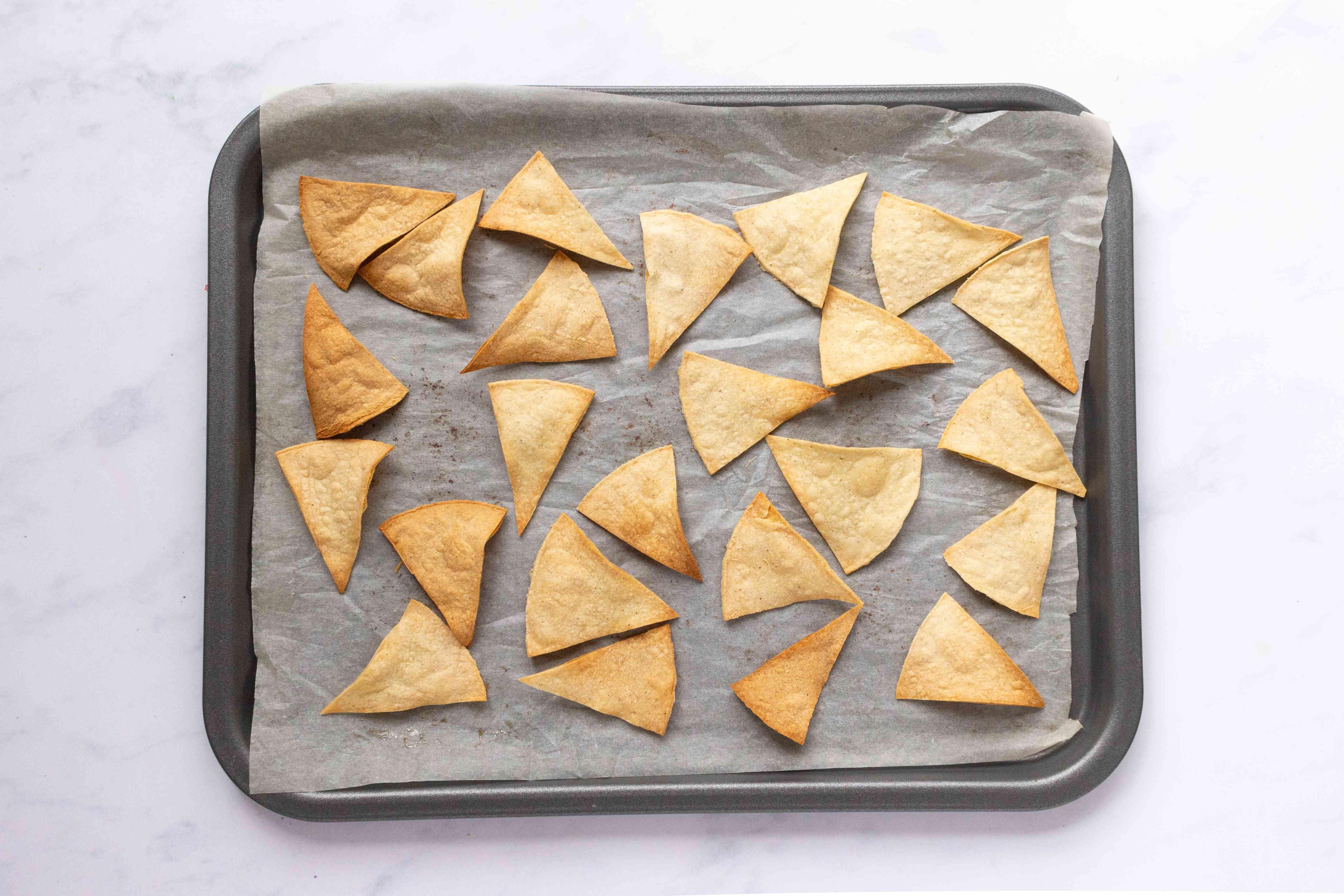 Homemade Totopos (Crunchy Corn Tortilla Chips) on a baking sheet