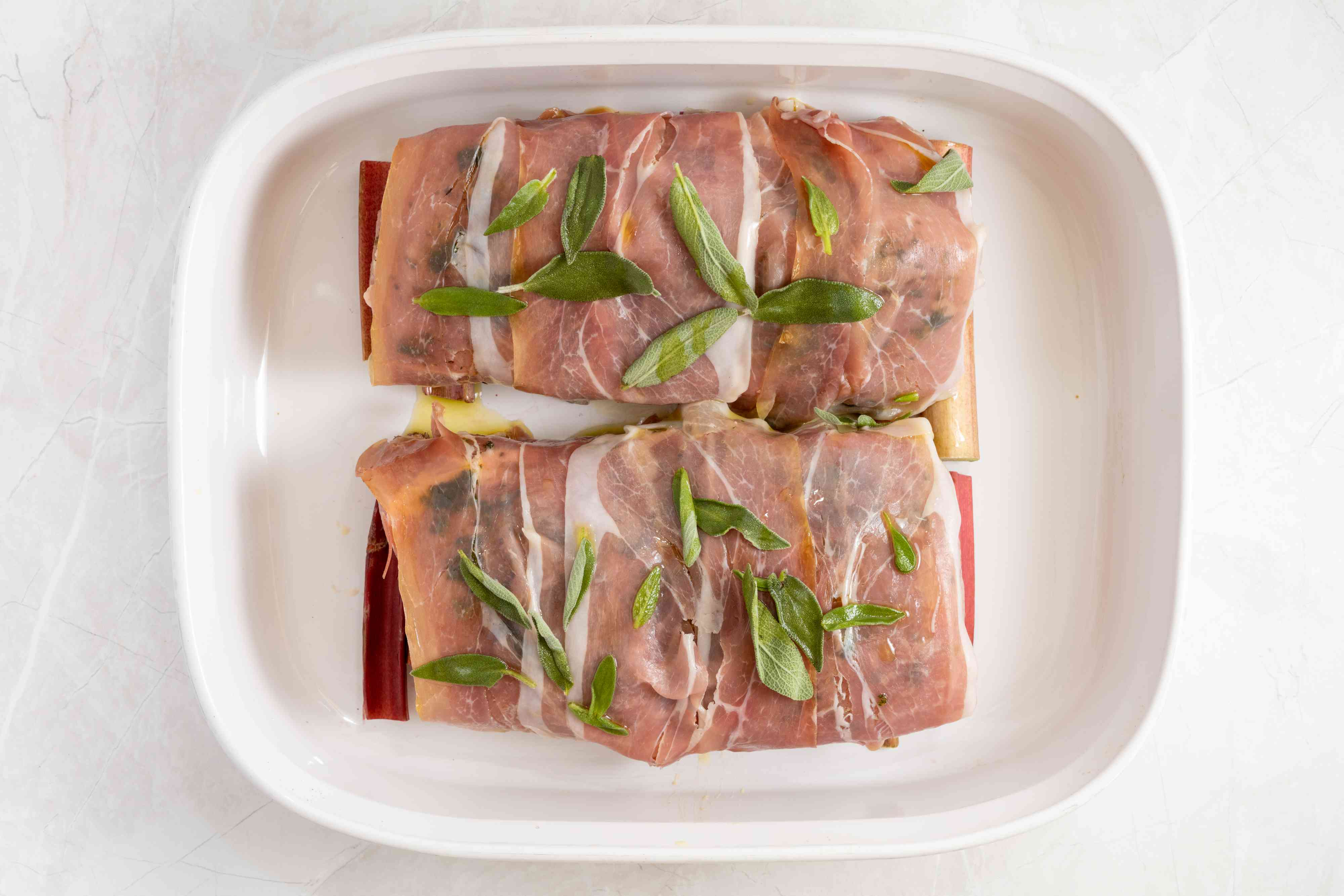 prosciutto wrapped pork in a baking dish, sprinkled with sage