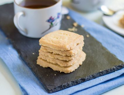Shortbread cookies and a cup of tea on a black slate