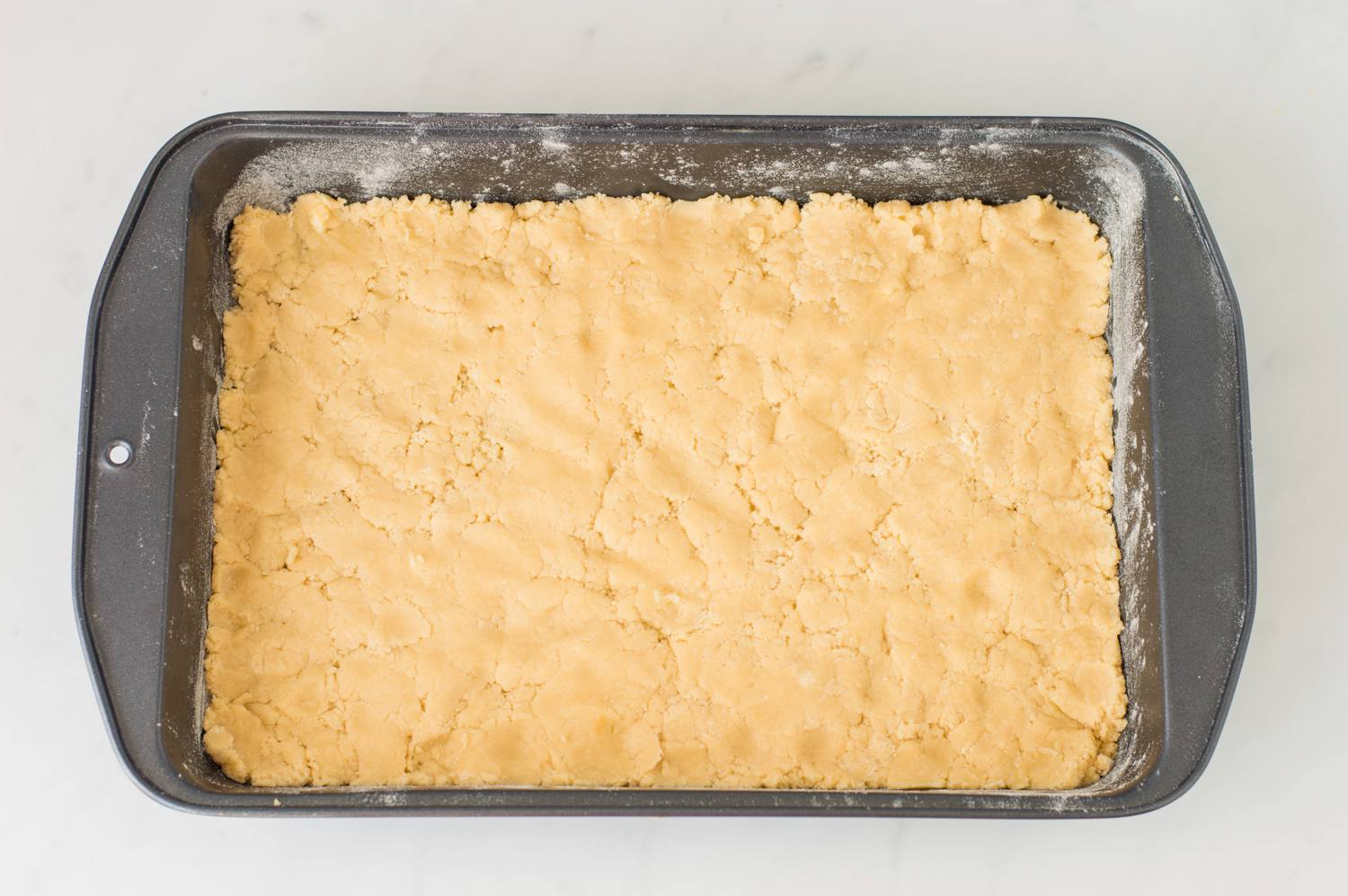 Cake mix patted down in a baking pan