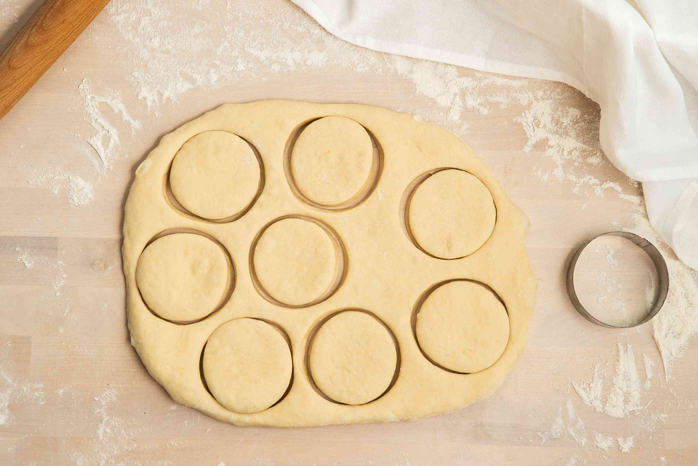 donuts cut out of dough with a donut cutter
