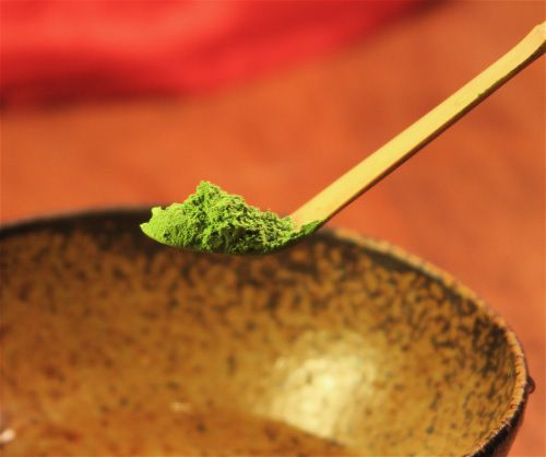 An image of Matcha, a powdered Japanese green tea on a wooden scoop, in front of a brown bowl.
