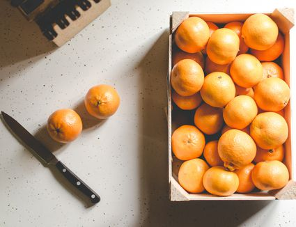 Small oranges in box with Knife