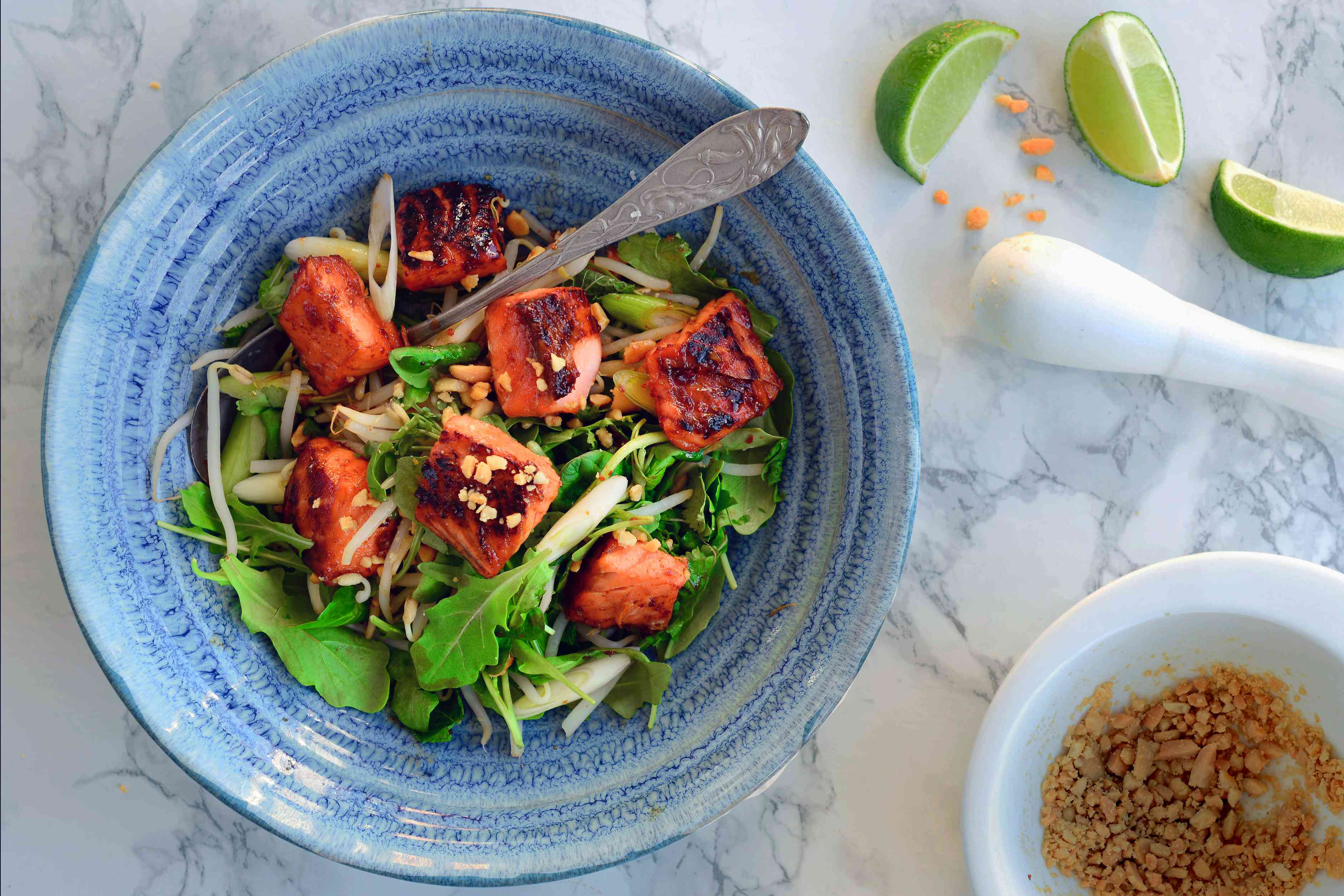 Caramelized salmon salad in a blue bowl with lime wedges