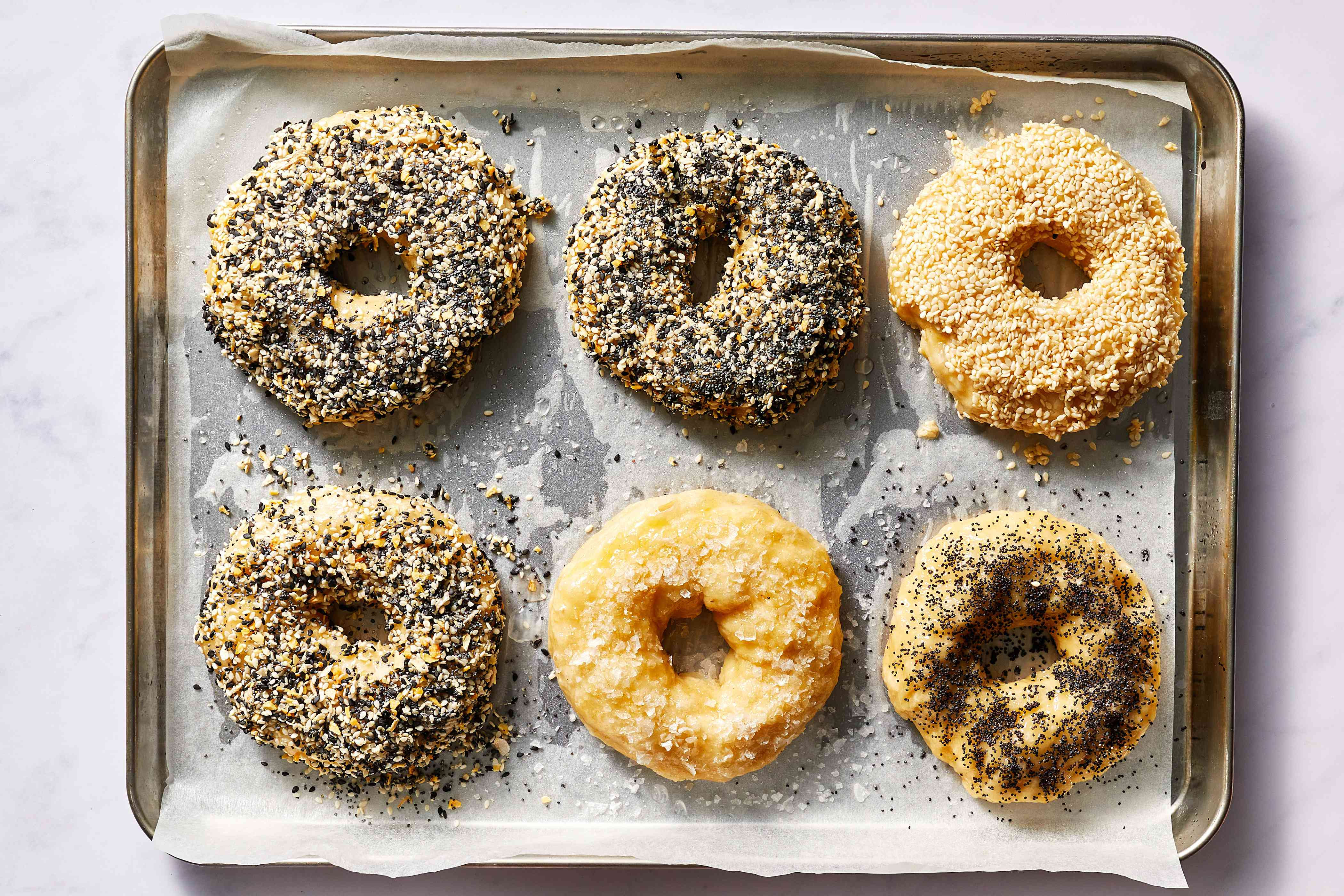 bagels with toppings on a baking sheet