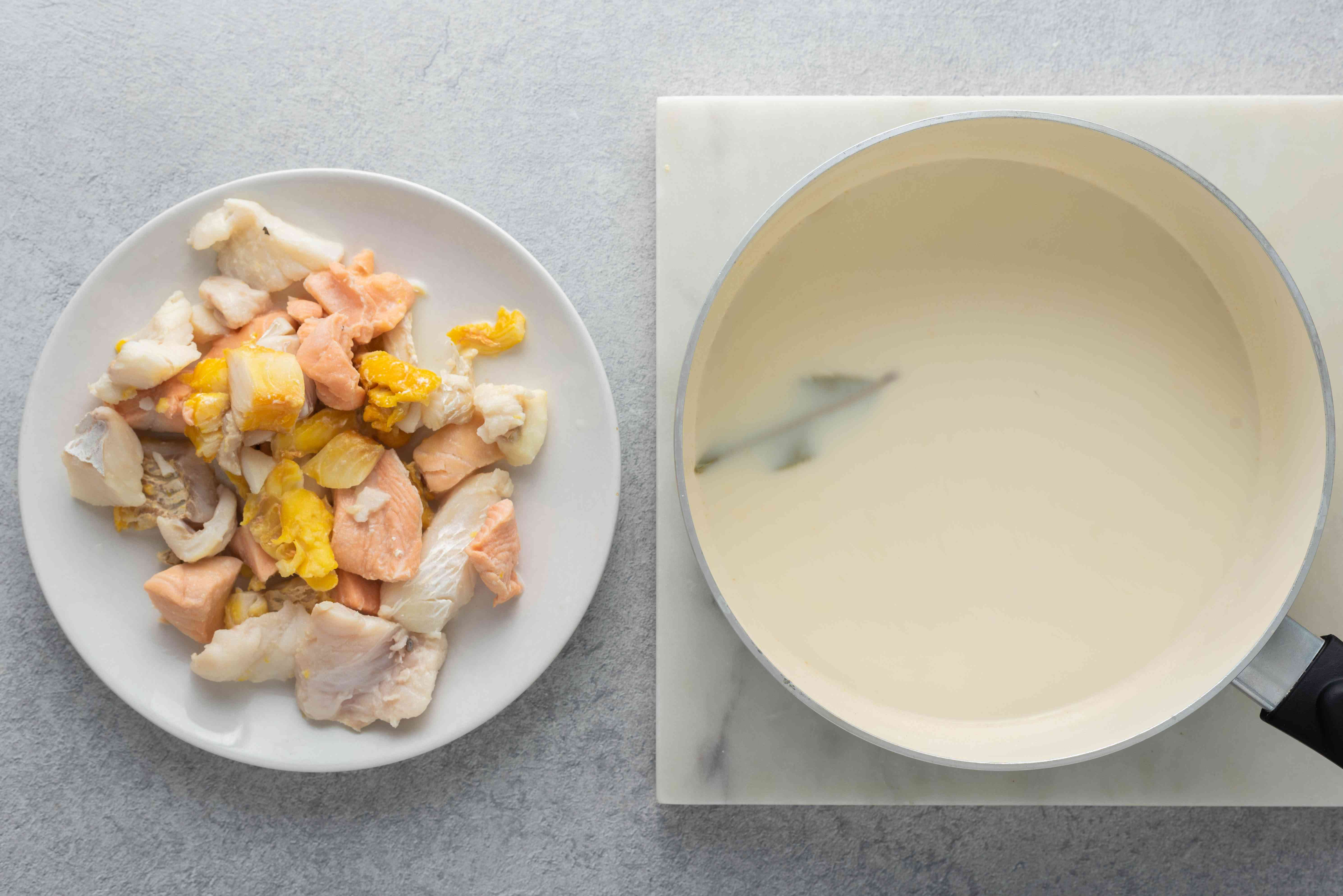 Poached fish on a plate; poaching liquid in a saucepan