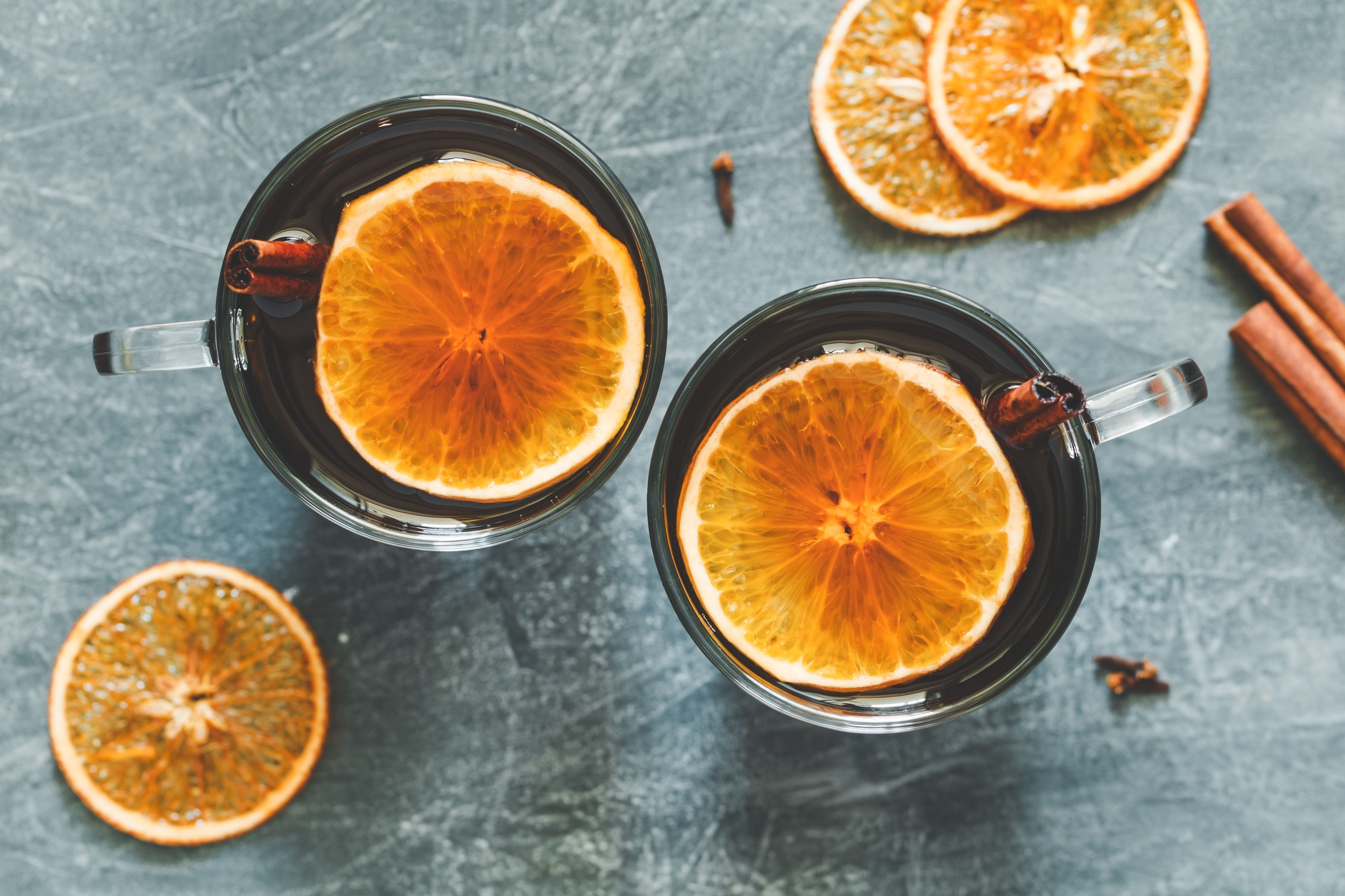 Mugs of homemade mulled wine with orange slices and cinnamon sticks