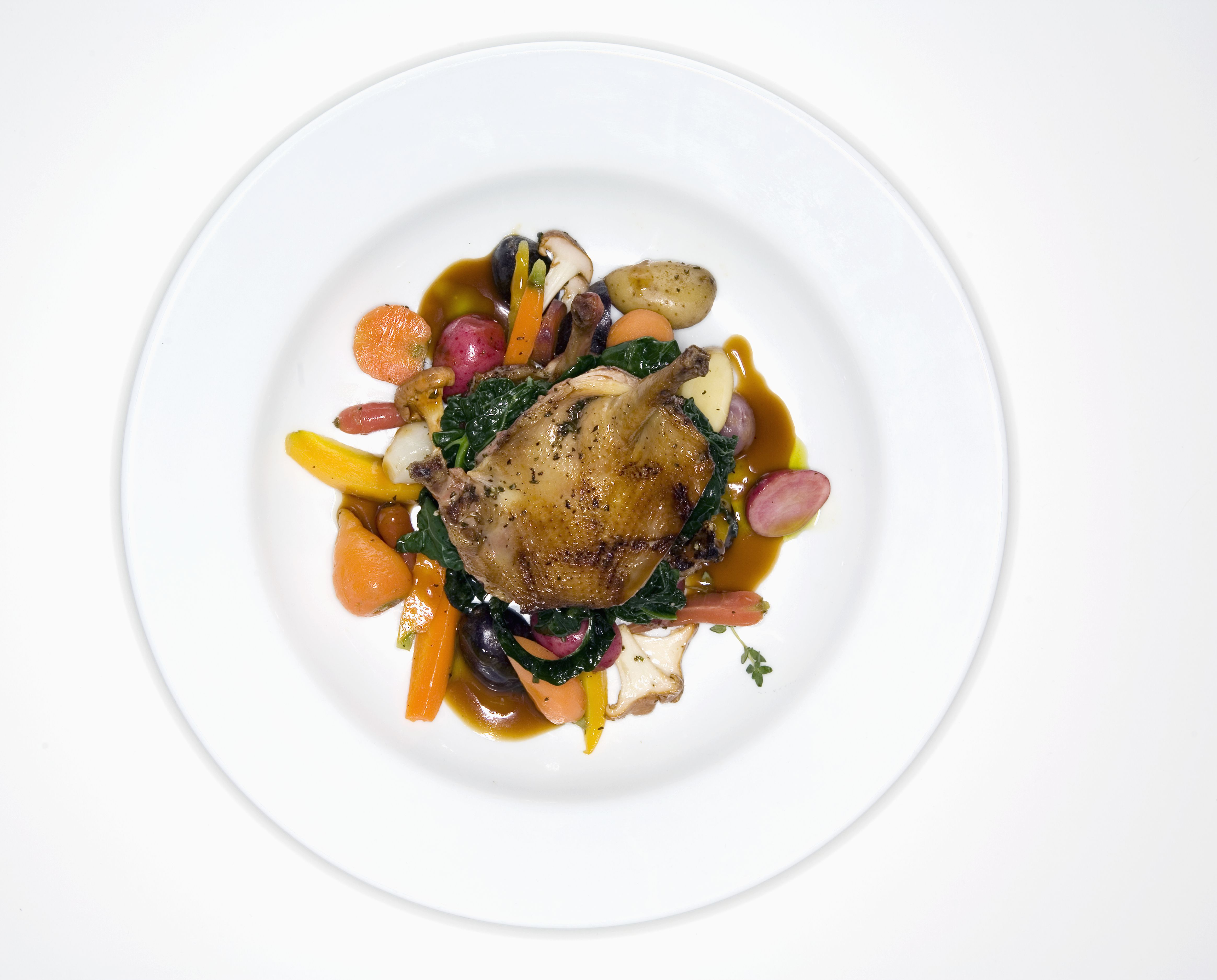 Cornish hen with vegetables on plate