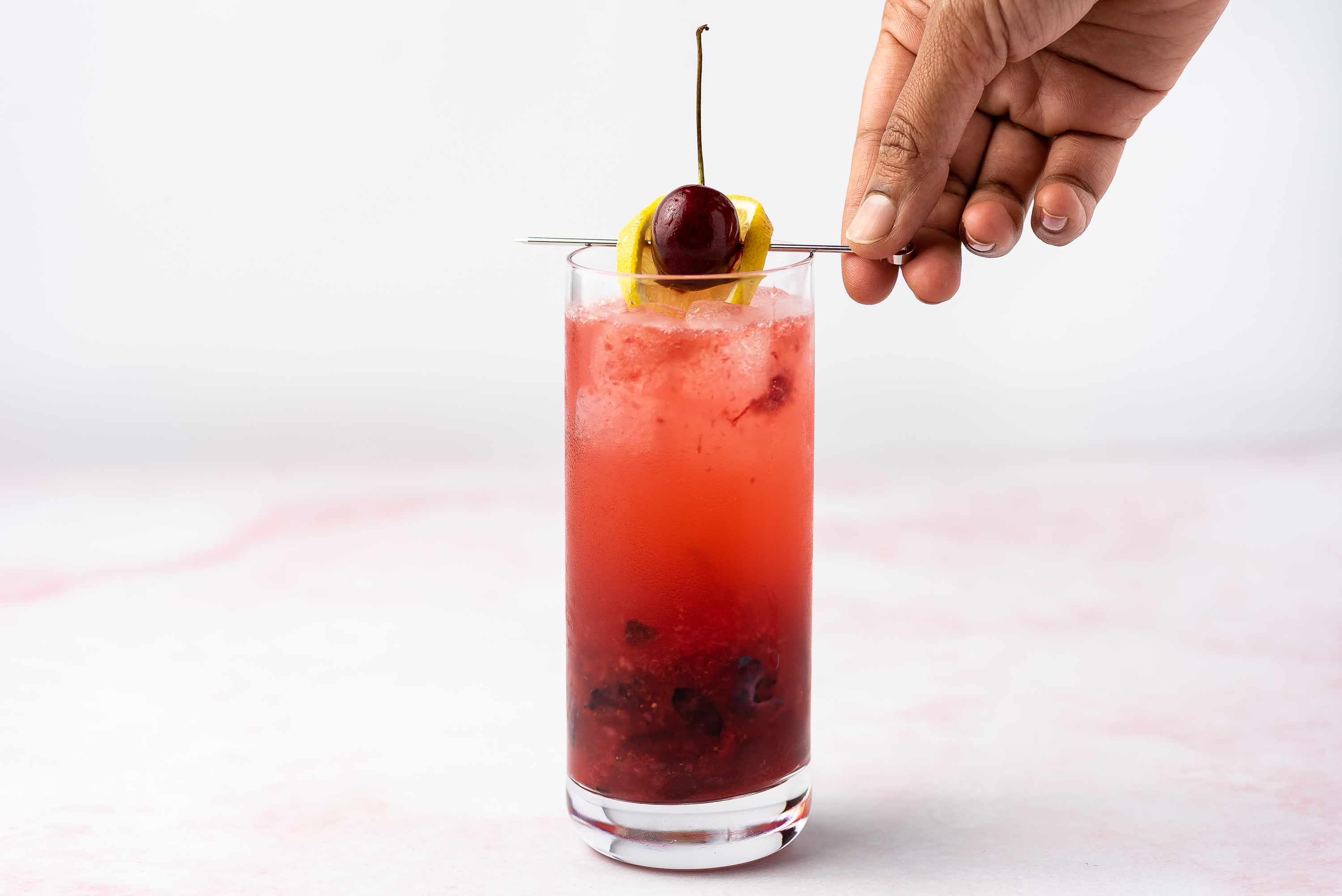 American Collins Cocktail, garnished with a lemon wheel and cherry
