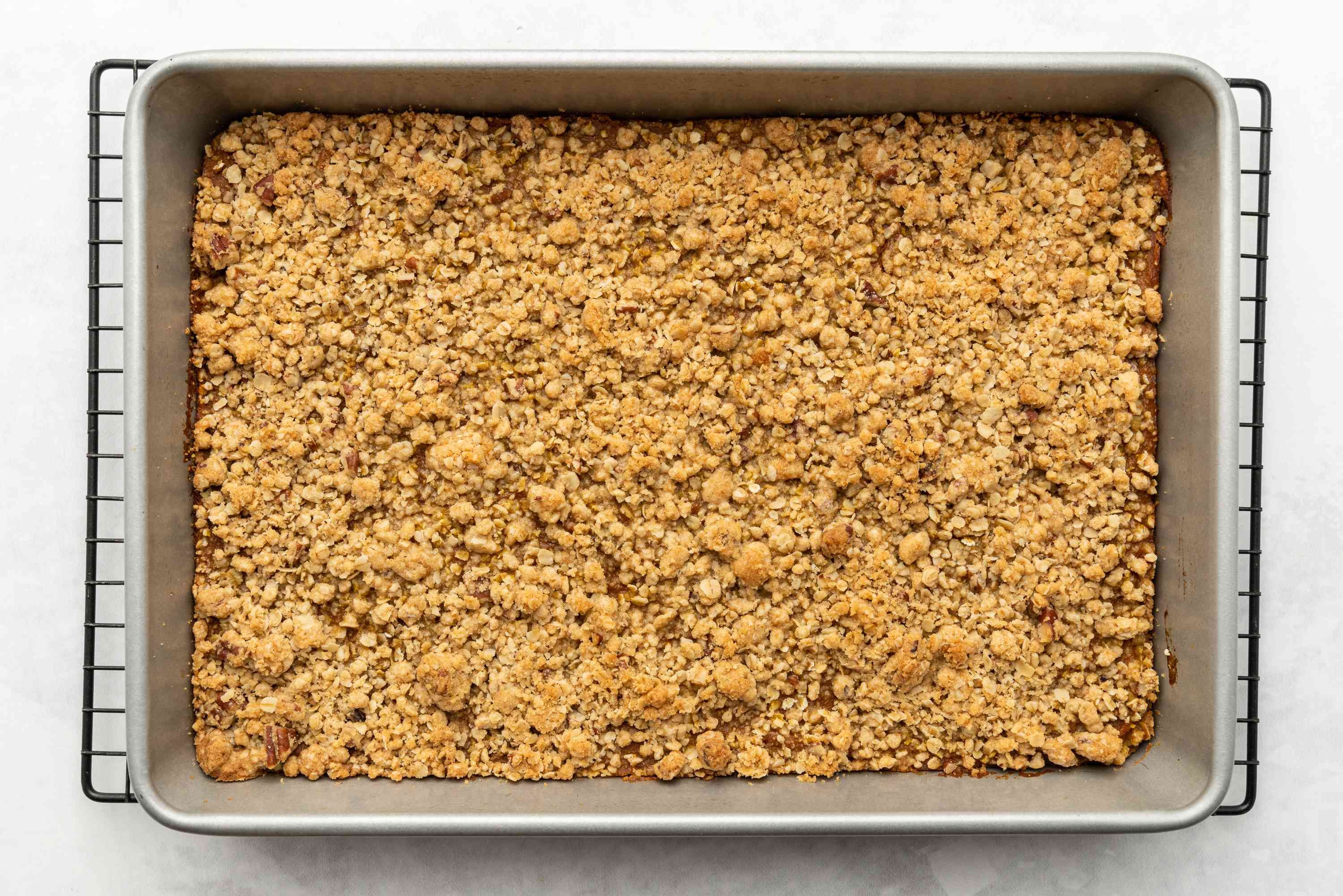 Pumpkin Squares With Oat Crust and Crumb Topping in a baking pan on a cooling rack