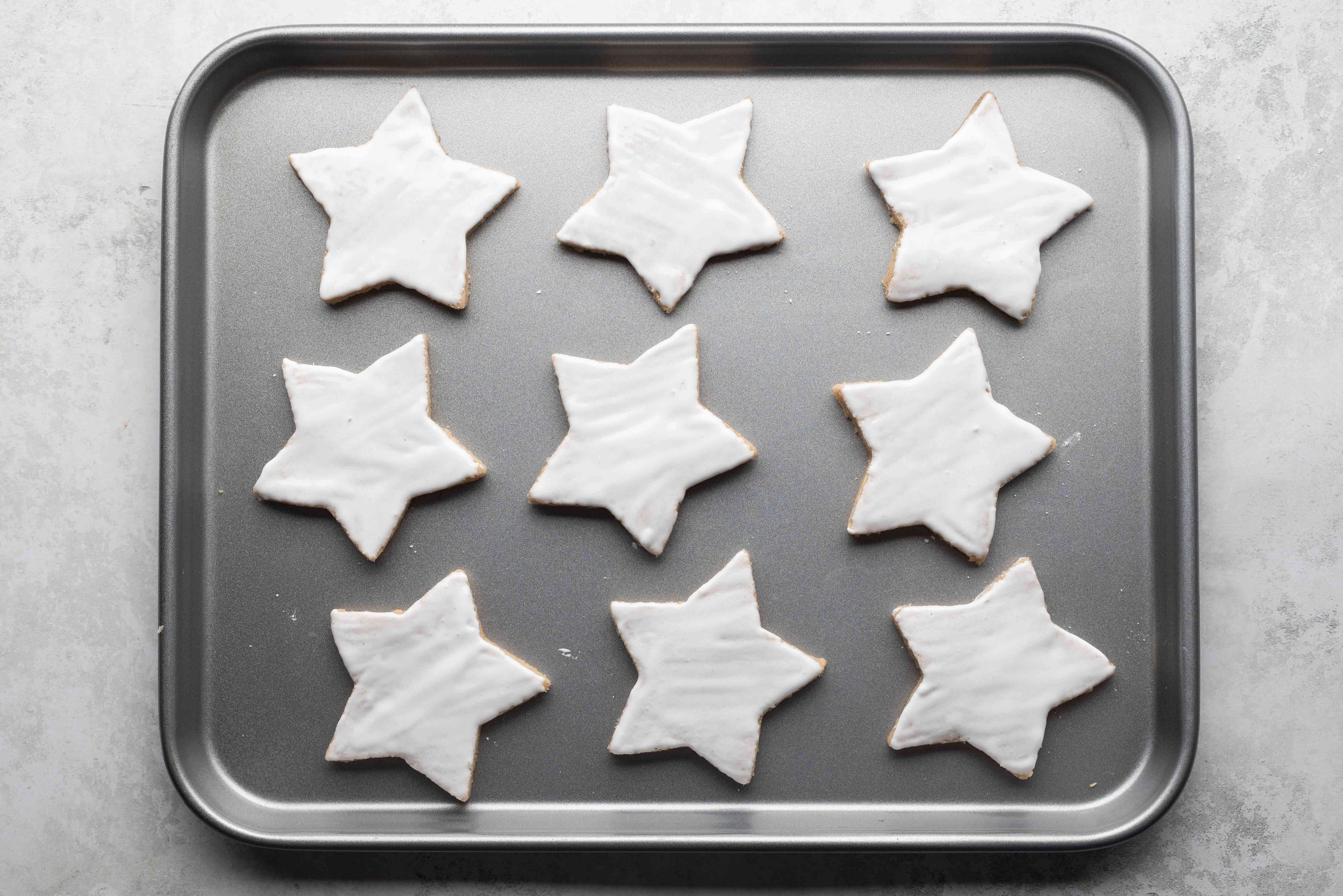cookies brushed with icing on a baking sheet