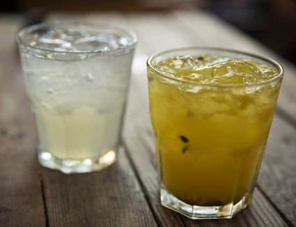 two glasses of mixed tequila drinks on a wooden table