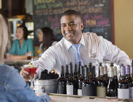 A friendly bartender serving a drink