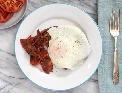 Over easy egg on a plate with bacon and broiled tomatoes.