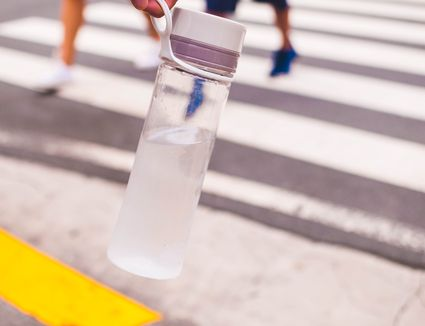 A close-up view of woman's hand holding a reusable water bottle on the street