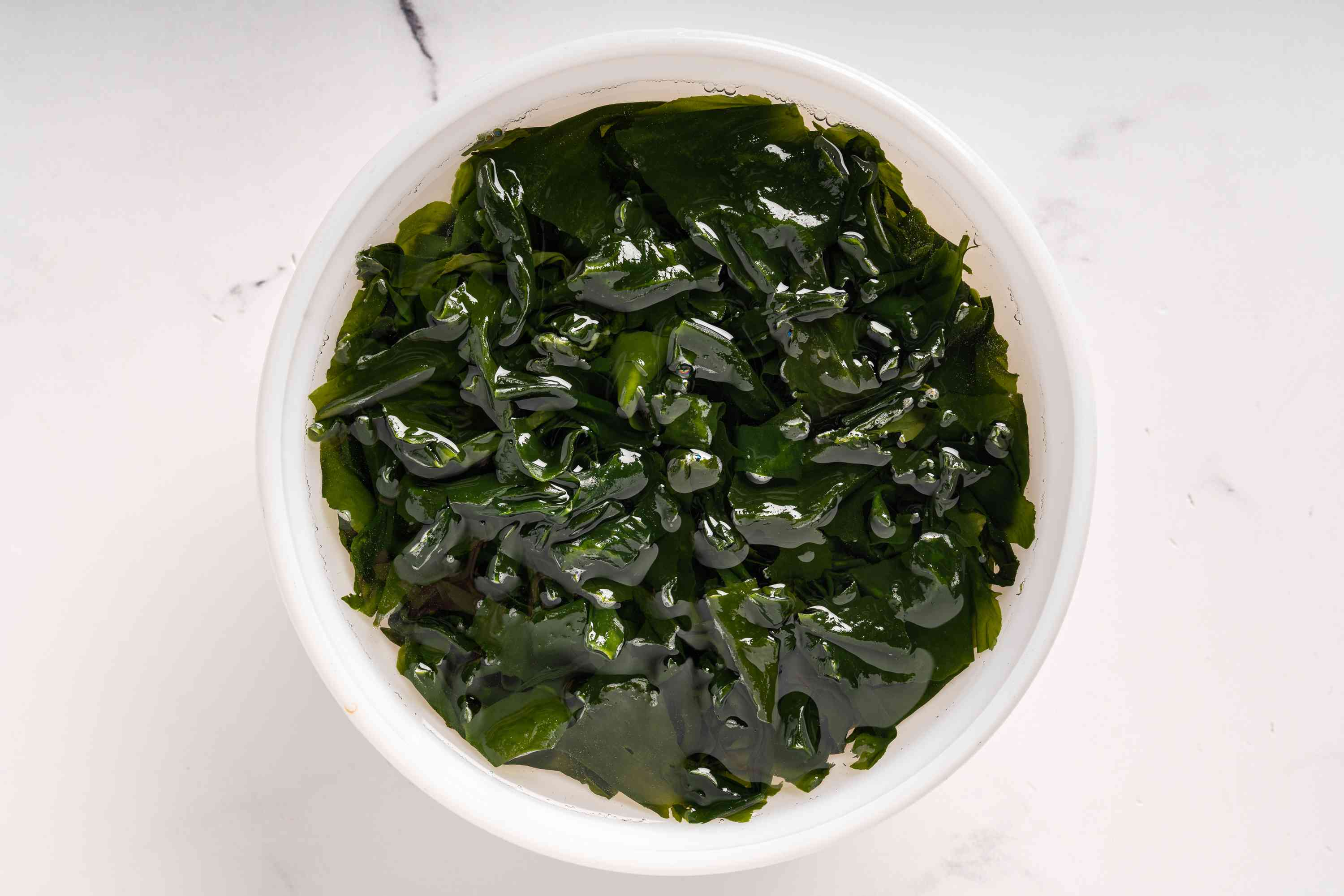 Rehydrate the seaweed by placing in a large bowl with water