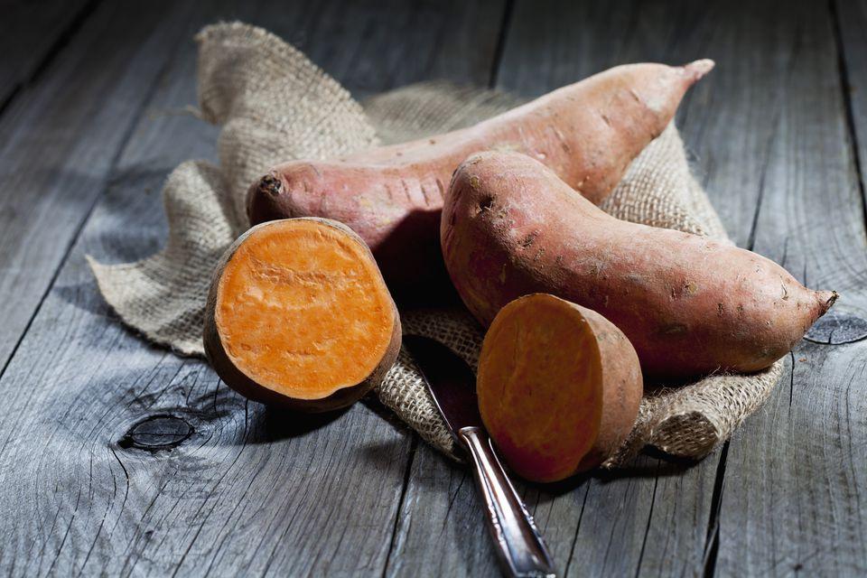 Raw sweet potato and knife on jute, wood