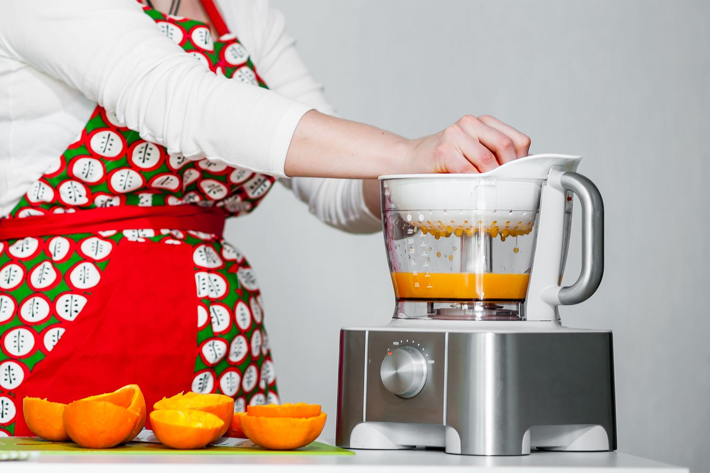 Juicing citrus fruits with an electric juicer.