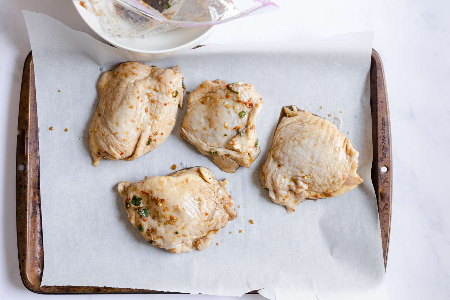marinated chicken on a parchment lined baking sheet