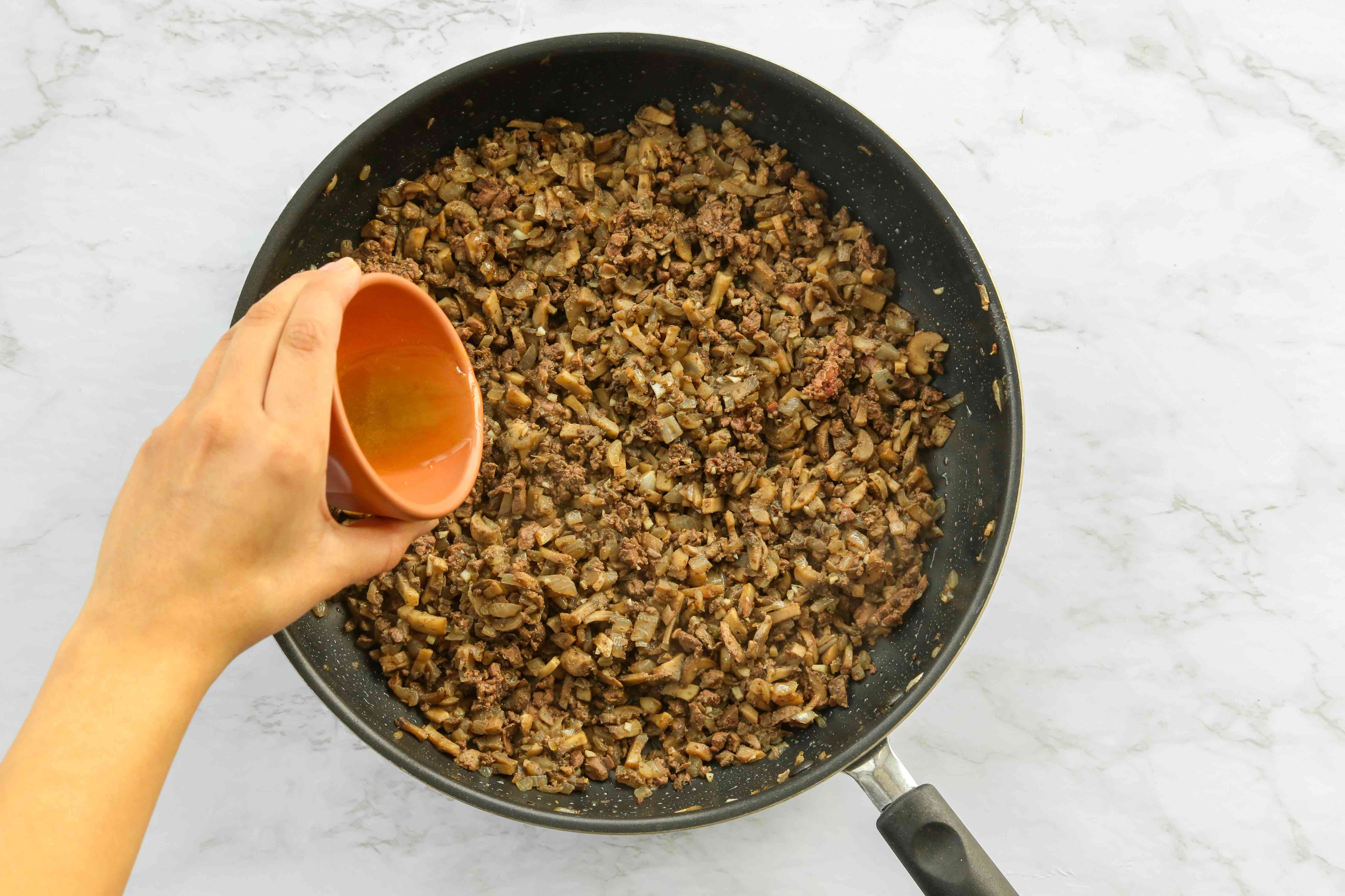 Add beef broth to the mushroom mixture