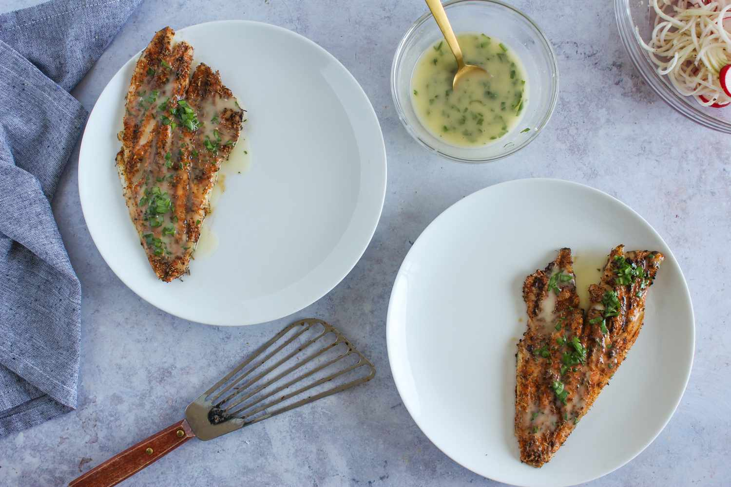Red snapper on plates with parsley and lemon butter