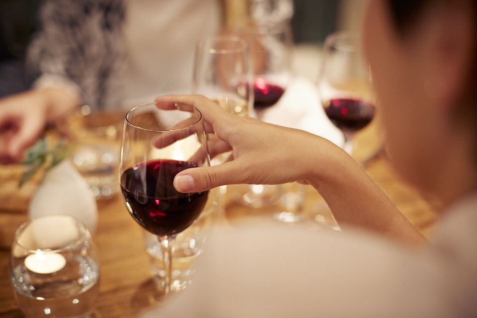 Close up of woman holding red wine at a group dinner