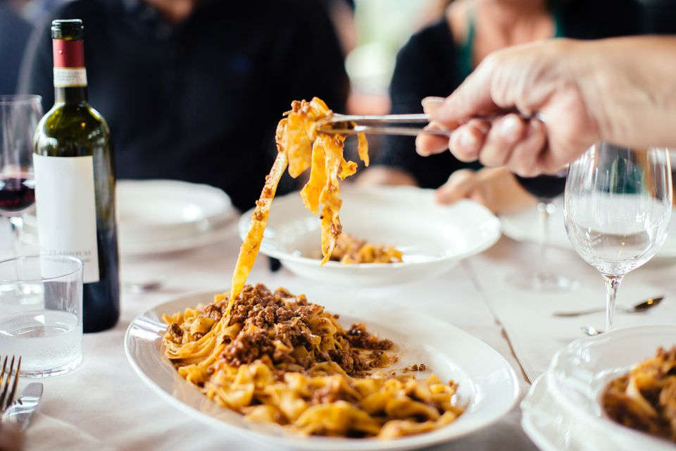 Tagliatelle al ragu' being served at a table