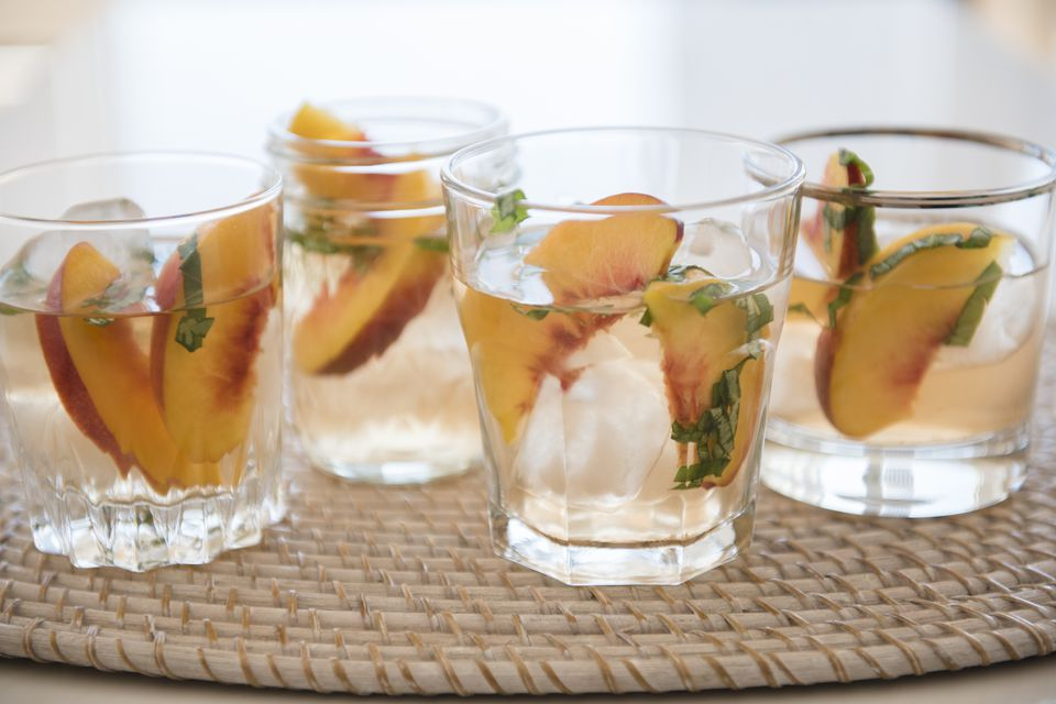 Cocktail with slices of peaches in drinking glasses