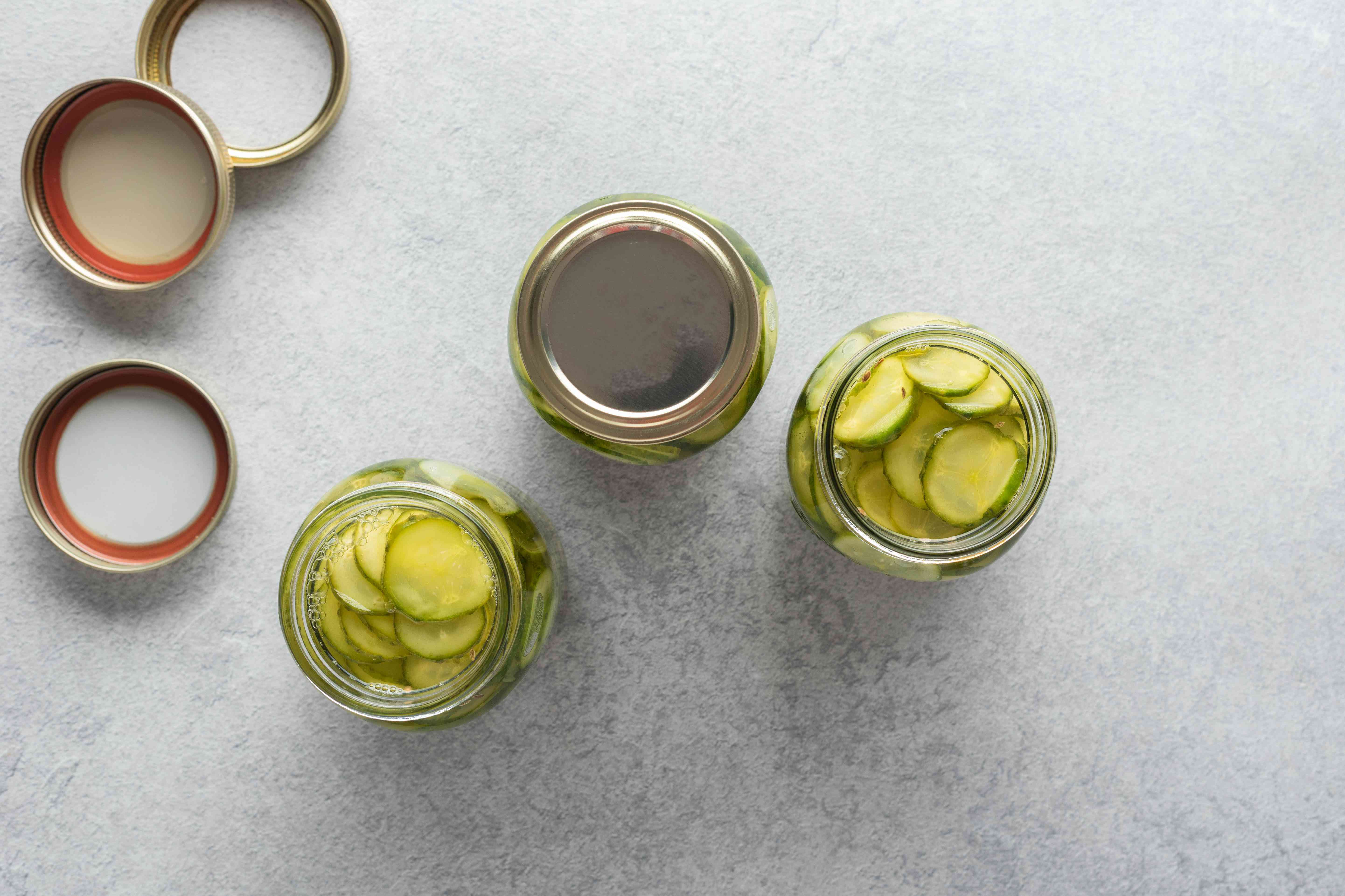hot vinegar mixture added to the cans with cucumbers