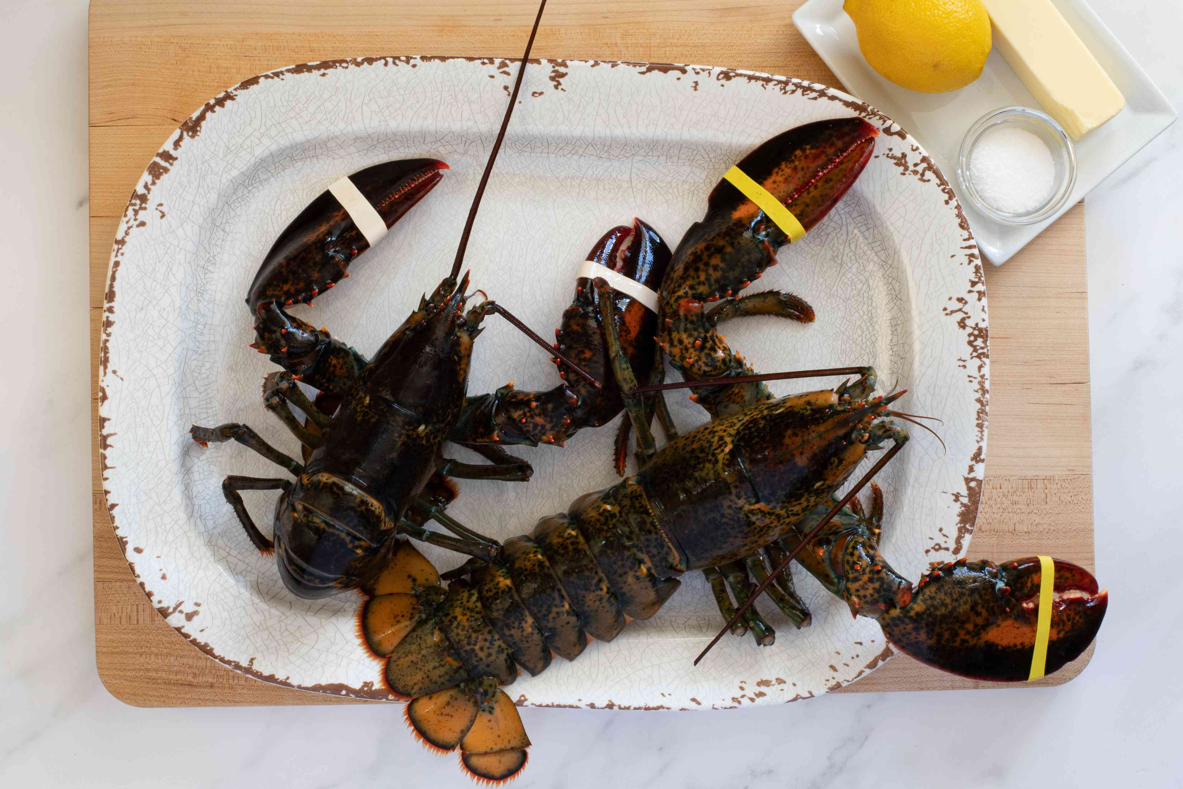 two live lobsters and ingredients for steamed lobsters