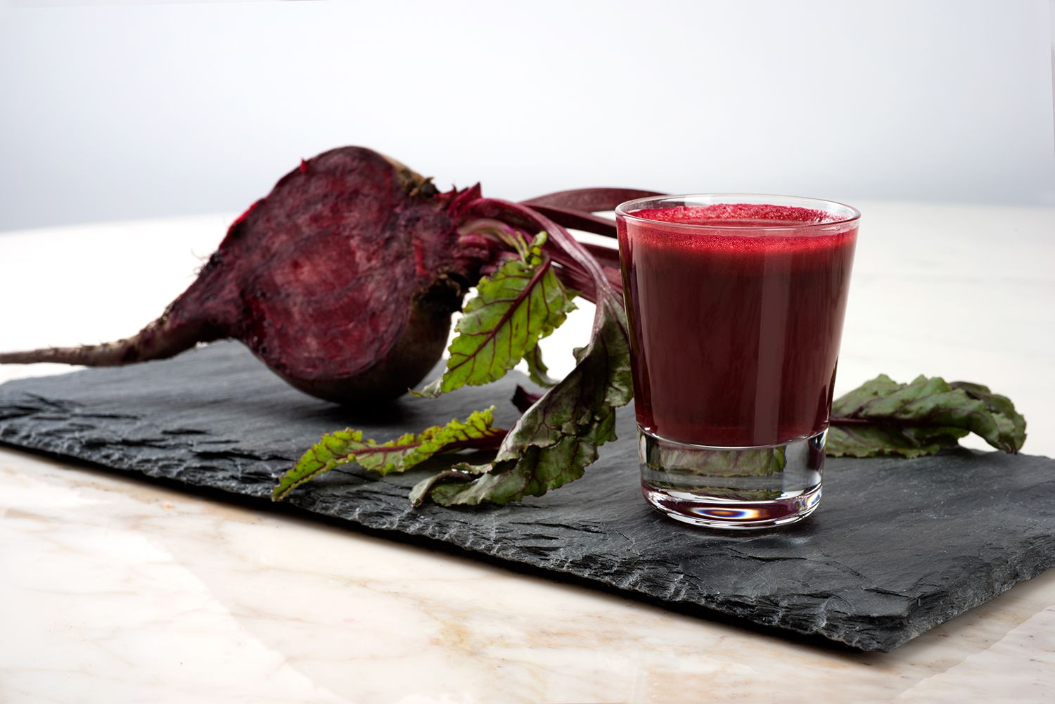 A glass of beet juice and a raw beet on a piece of slate