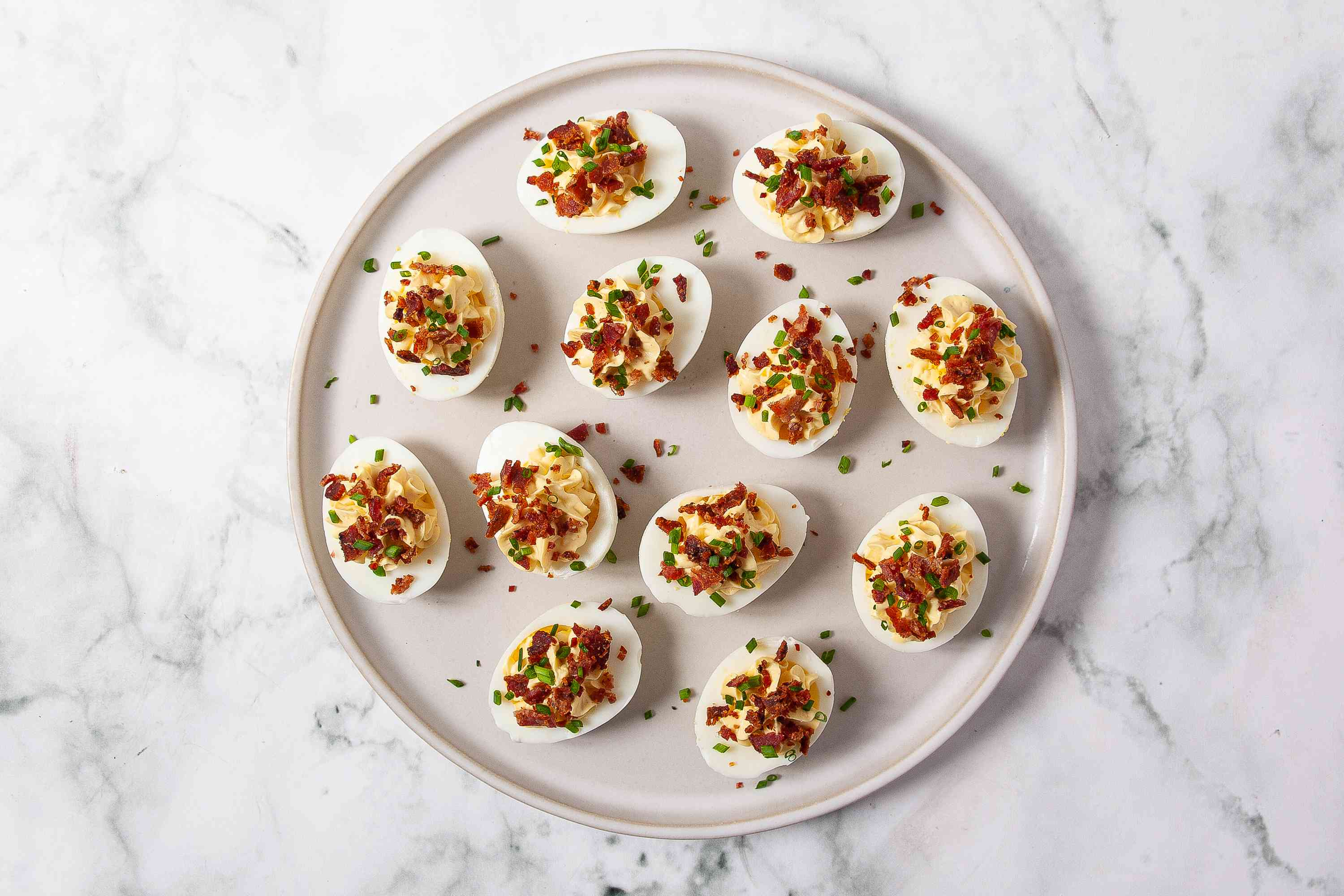 Deviled eggs sprinkled with bacon and chives