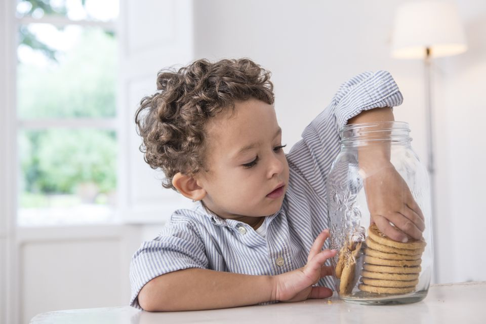 Boy getting biscuit from cookie jar