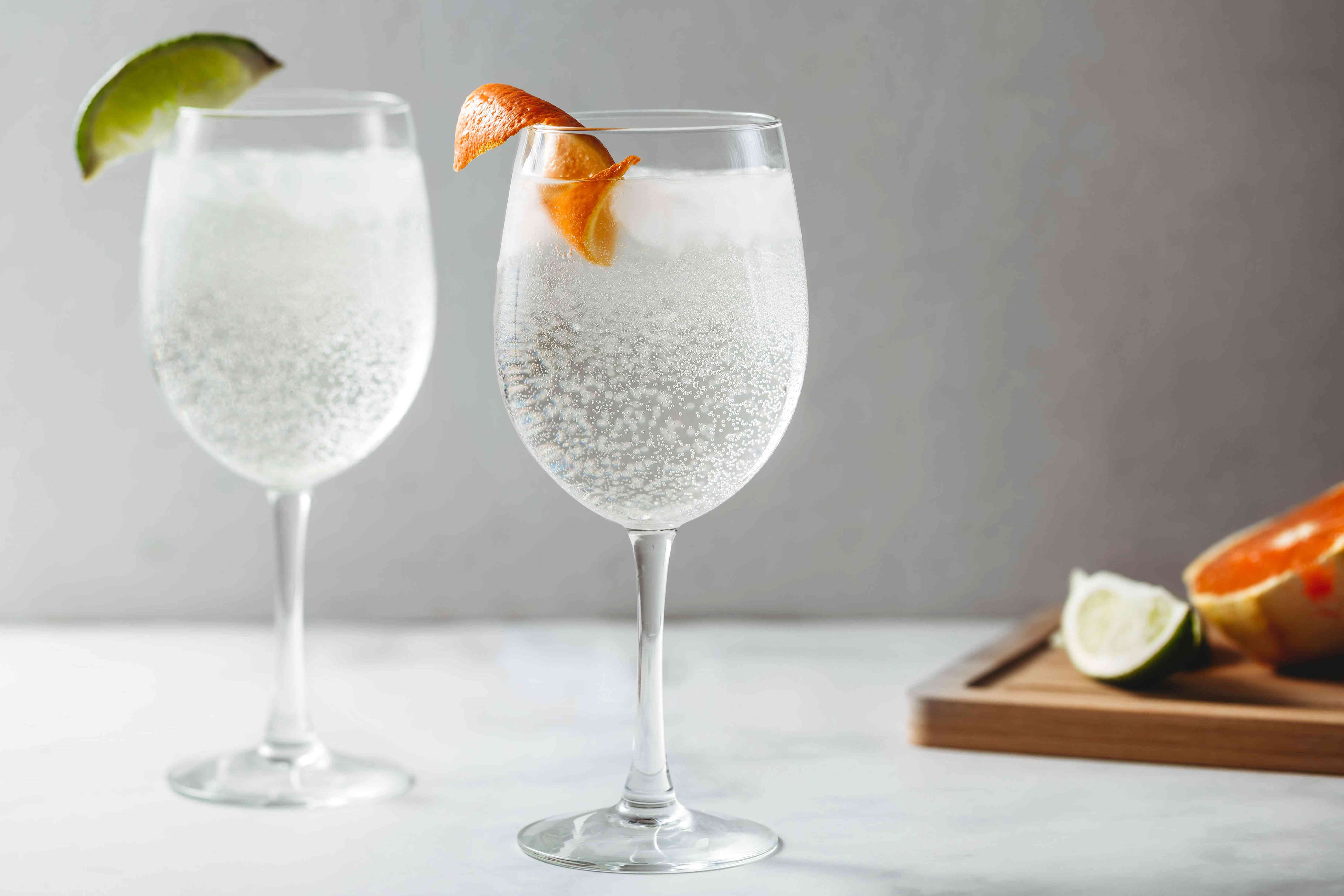 White wine spritzers garnished with lime and orange peel