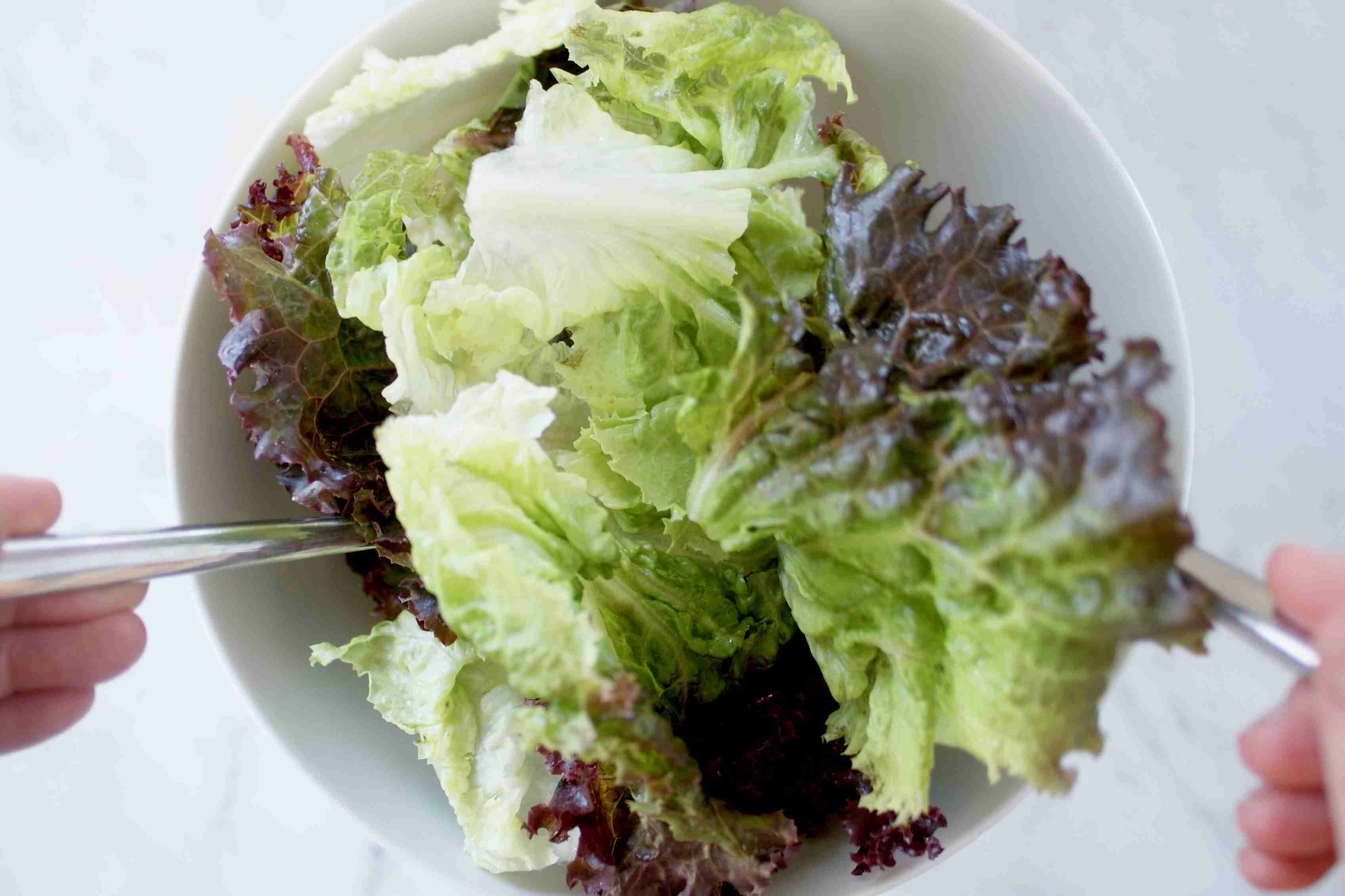 Dressing a salad with tongs