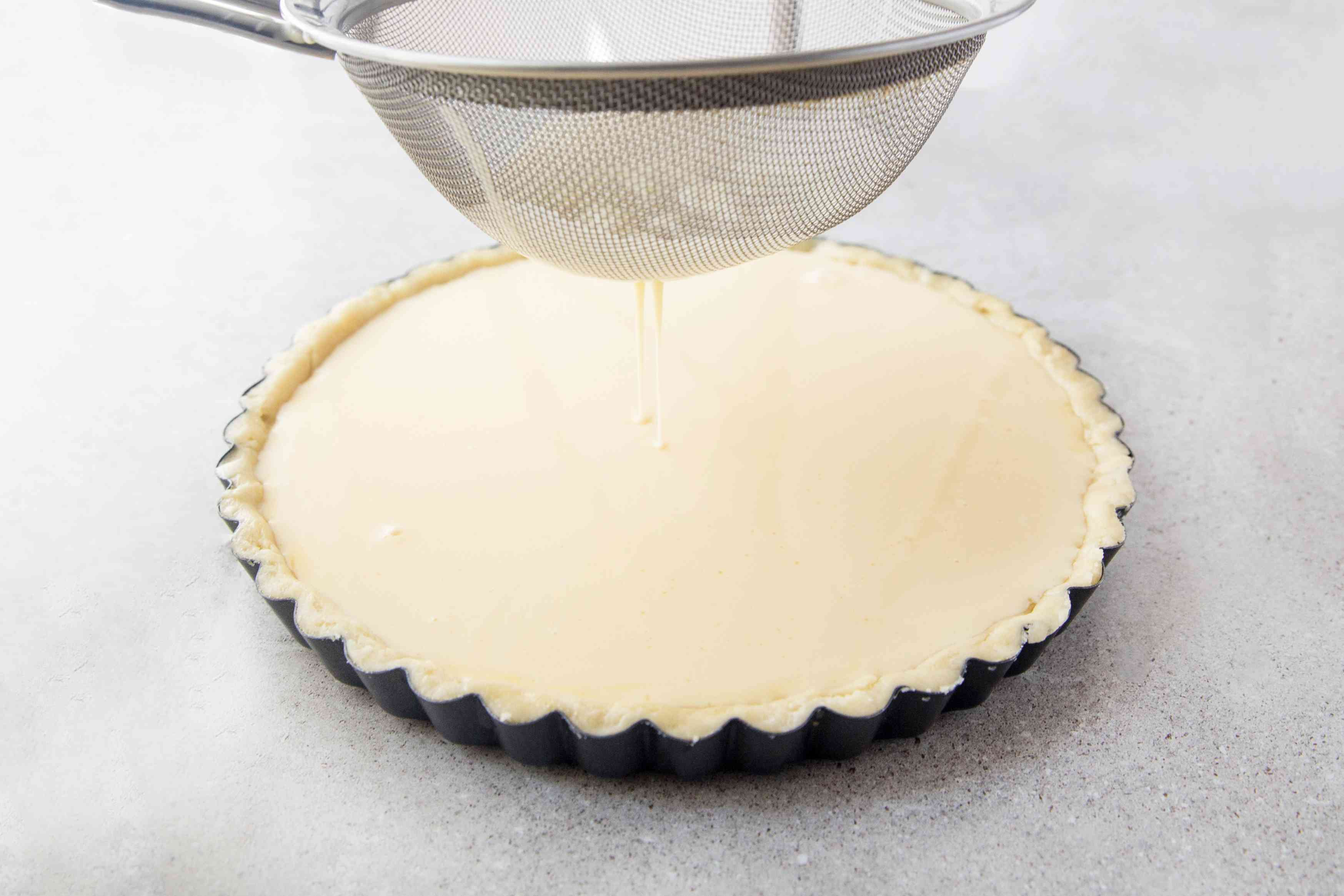 Pouring egg and cream into pastry case