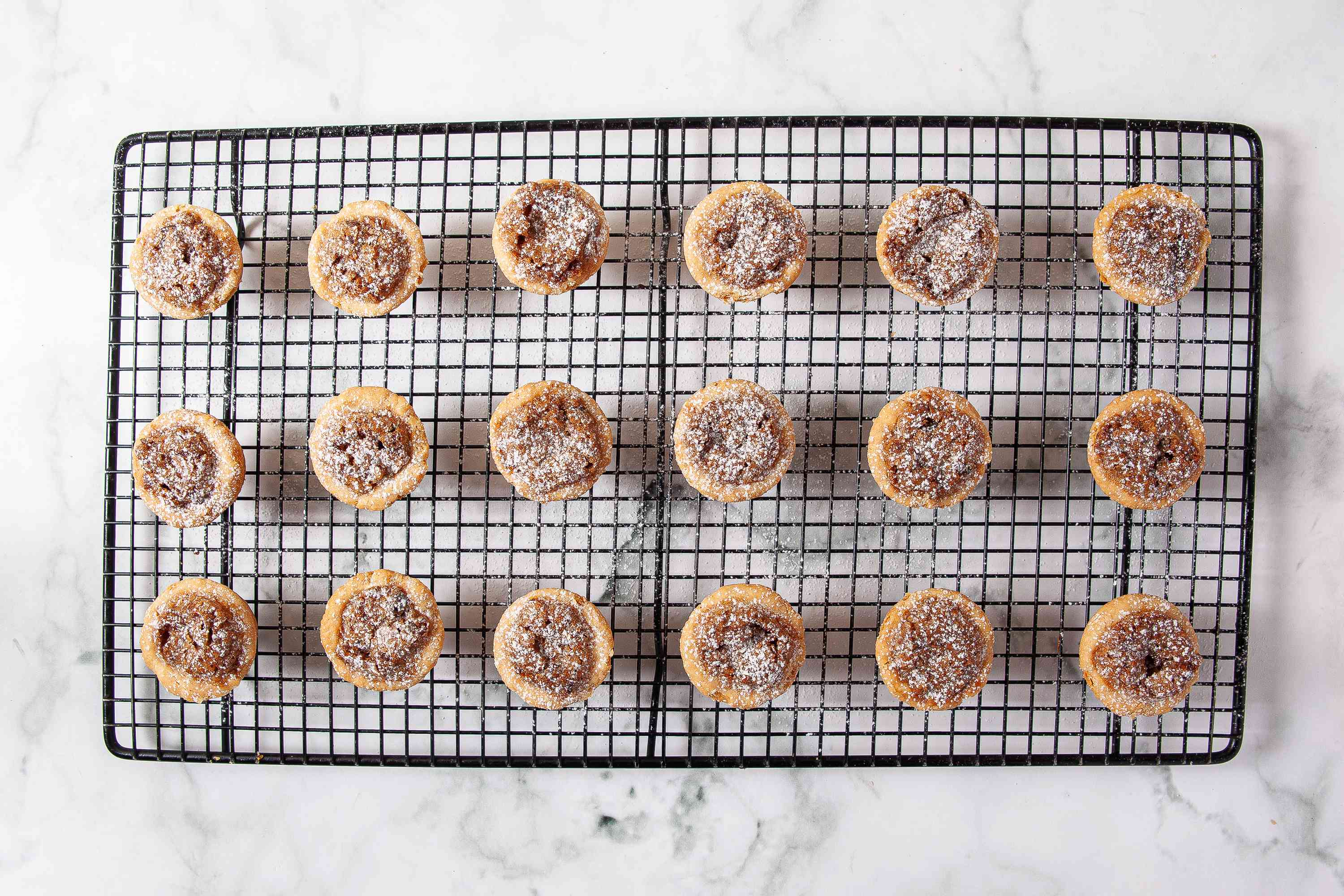 Pecan Tassies dusted with powdered sugar