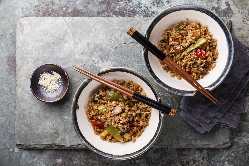 Fried Rice with vegetables and sesame on stone slate background