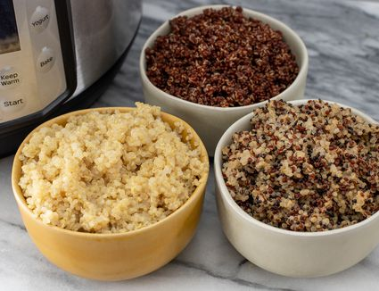 a variety of quinoa colors in bowls next to an instant pot pressure cooker