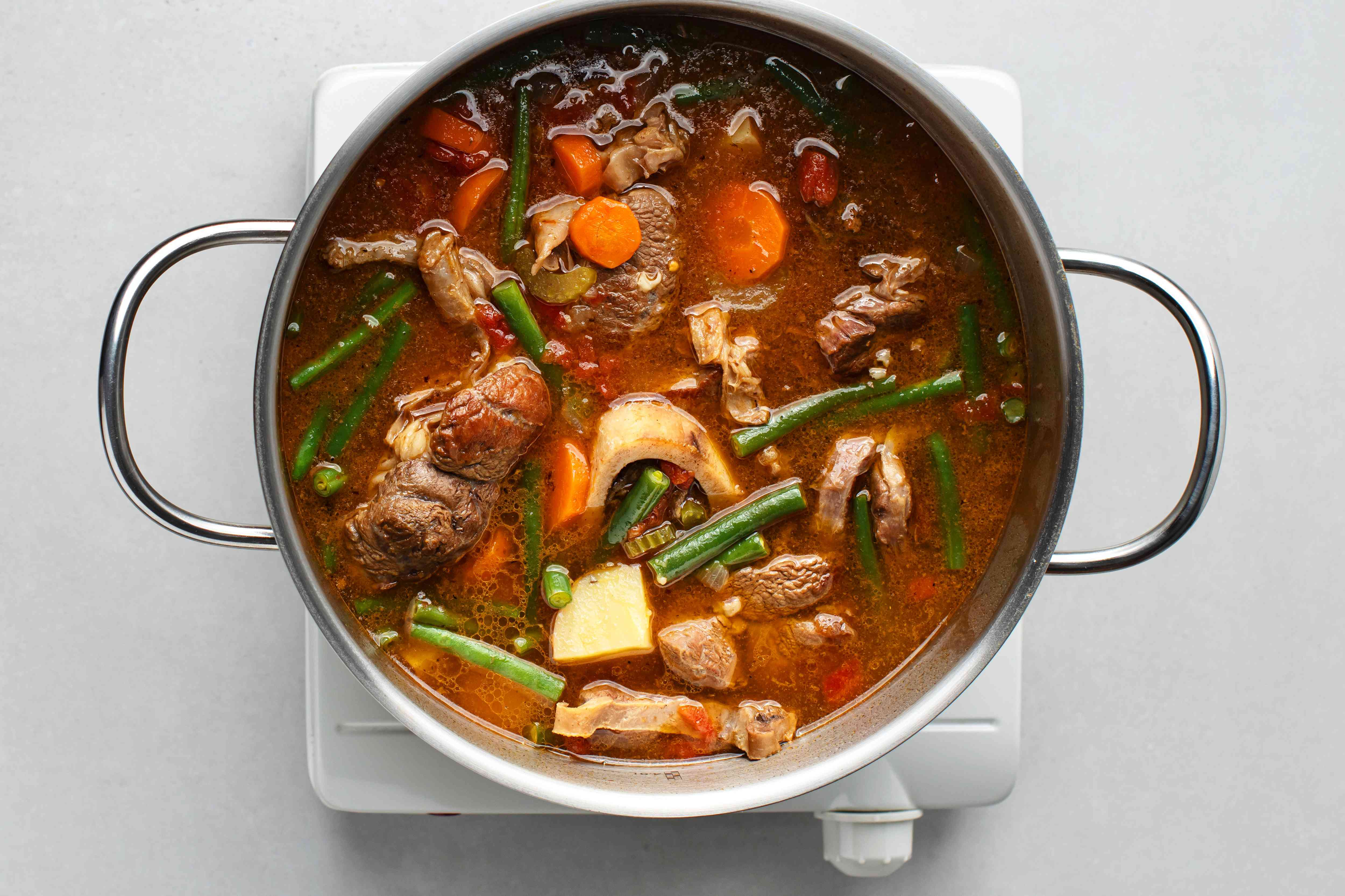 Add the carrots, string beans, potatoes, celery, tomatoes, and rice into the beef-and-onion mixture