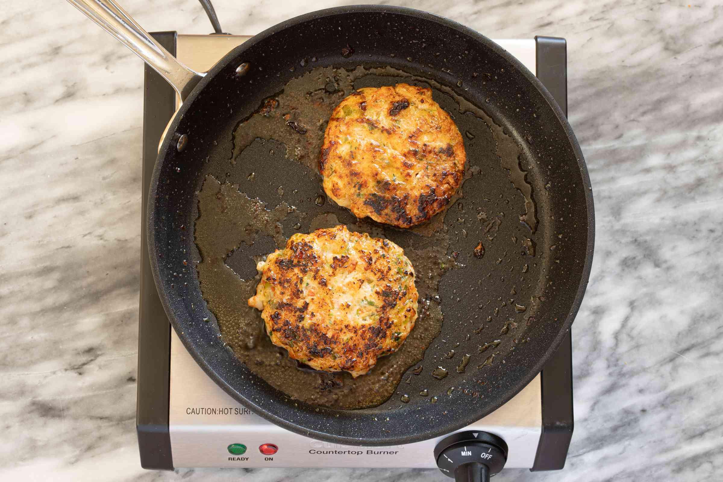 Shrimp burger patties in skillet.
