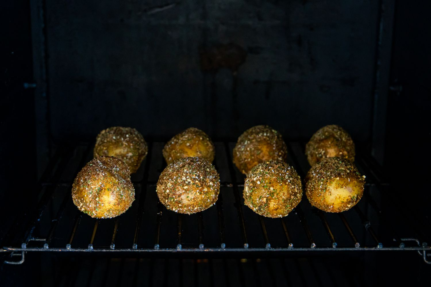 Herb covered potatoes in a smoker