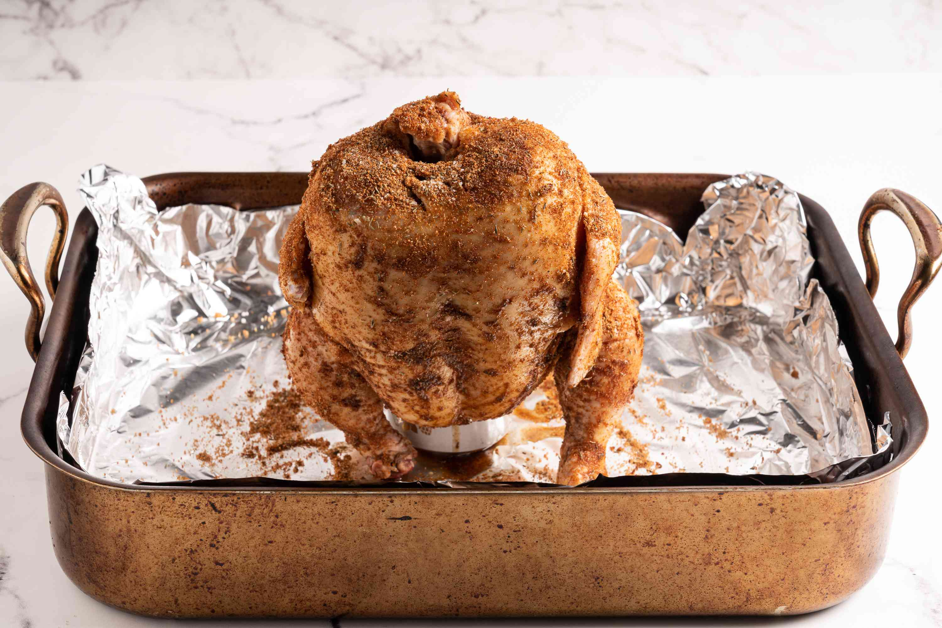 Stand up the chicken with the large cavity down and place it on top of the half-filled can