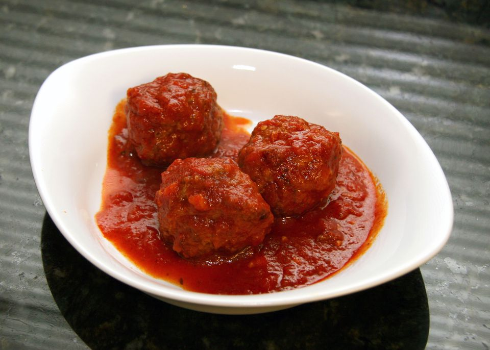 Maria's Meatballs with red gravy in a white serving bowl