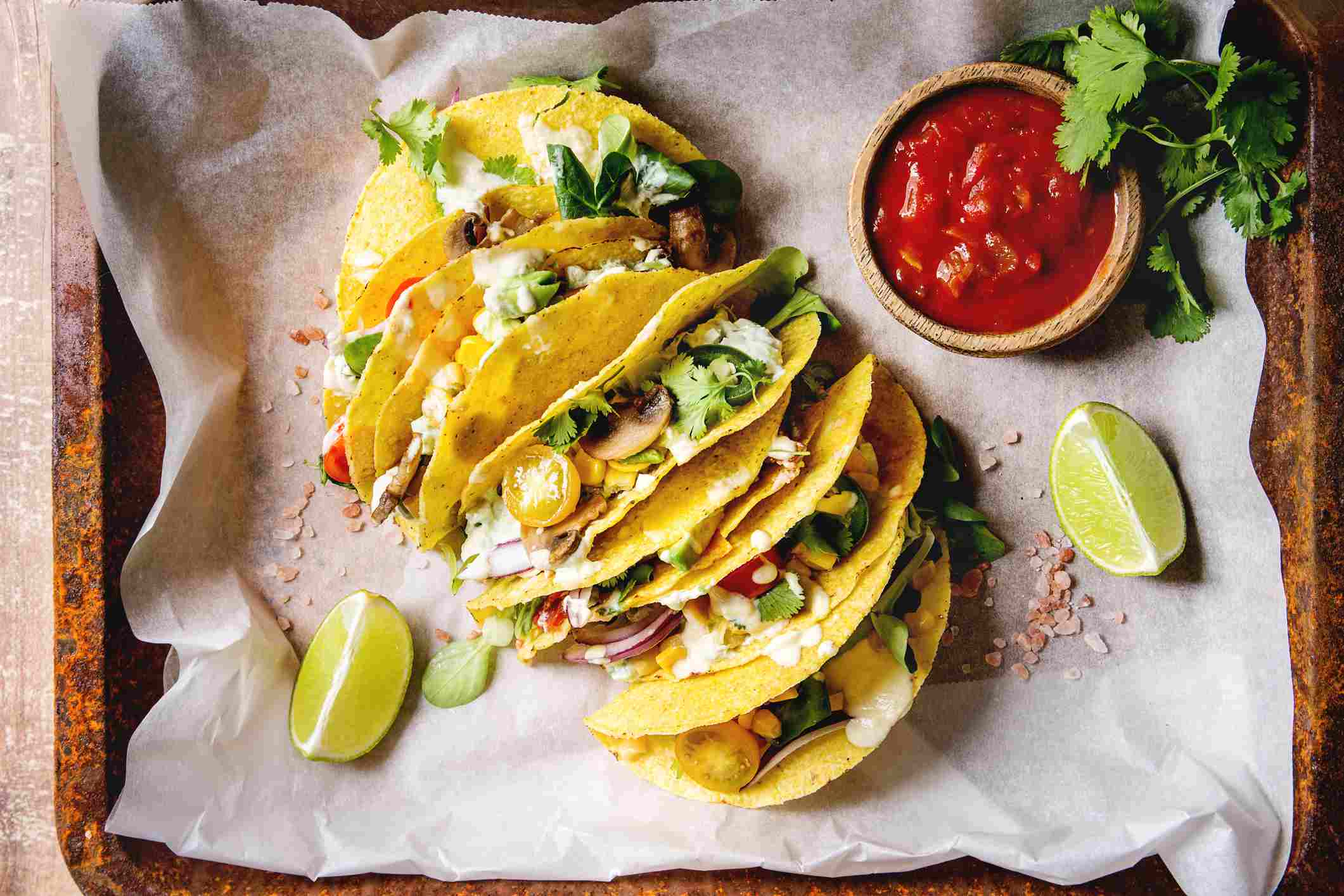 Vegetarian corn tacos with salsa and lime wedges