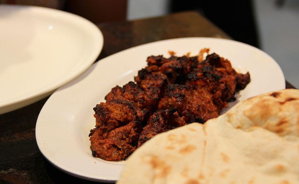 Bihari Kabab on a plate next to naan.