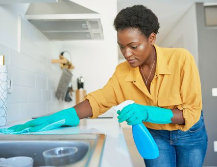 black woman cleaning kitchen